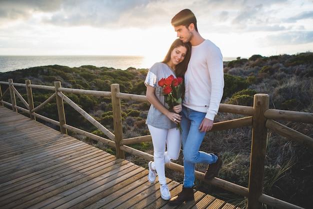 Paar zu fuß auf einer holzbrücke bei sonnenuntergang