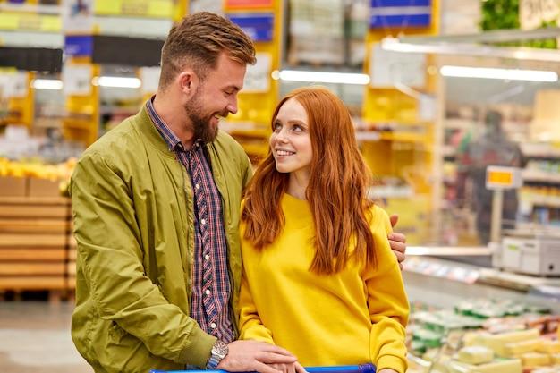 Paar zu fuß in lebensmittelgeschäft wählen lebensmittel für zu hause, sie sehen sich mit liebe, lächelnd
