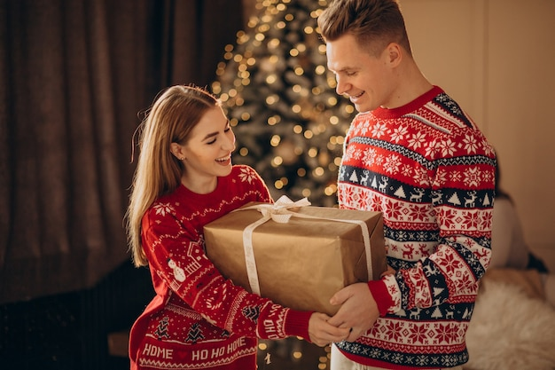 Paar zusammen mit weihnachtsgeschenken durch den weihnachtsbaum
