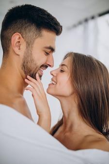 Paar zusammen umarmt unter weißer decke
