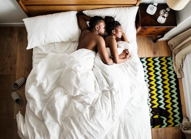 Paare afrikanischer abstammung, die auf dem kuschelnden und umarmenden bett schlafen