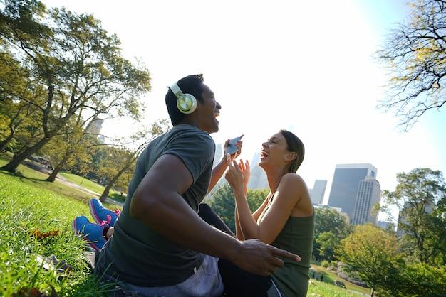 Paare am central park hörend musik auf smartphone