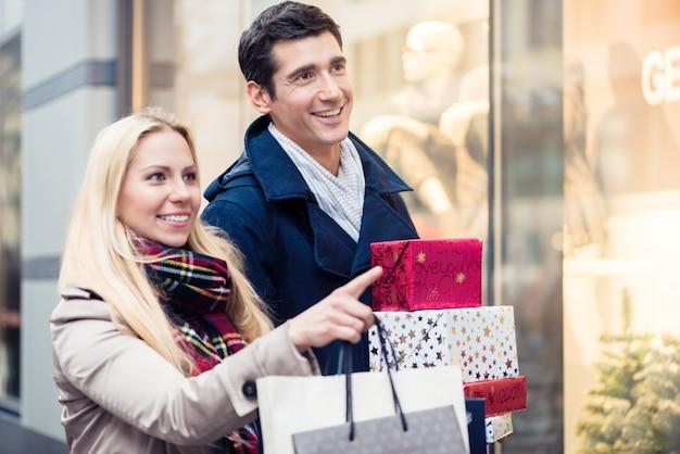 Paare am shopfenster, das weihnachtseinkaufen tut