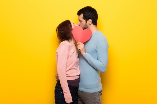Paare am valentinstag, der ein herzsymbol und ein küssen hält