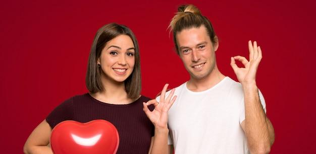 Paare am valentinstag, der ein okayzeichen mit den fingern über rotem hintergrund zeigt
