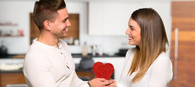 Paare am valentinstag, der geschenkbox in einem haus hält