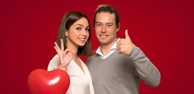Paare am valentinstag, der okayzeichen mit zeigt und einen daumen herauf geste gibt