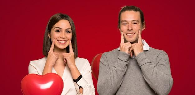 Paare am valentinstag lächelnd mit einem glücklichen und angenehmen ausdruck über rotem hintergrund