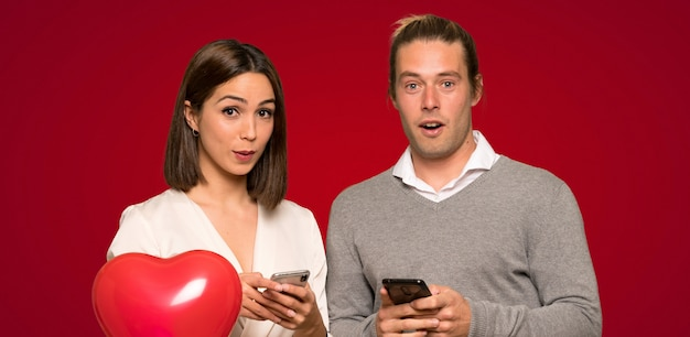 Paare am valentinstag überrascht und eine mitteilung über rotem hintergrund sendend