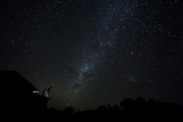 Paare auf der dachspitze, die mliky weise und sterne im nächtlichen himmel auf bali-insel aufpasst.