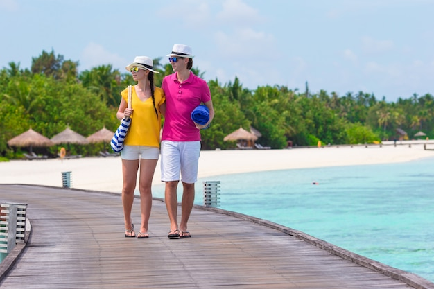 Paare auf der tropischen strandanlegestelle, die zum strand bei malediven geht