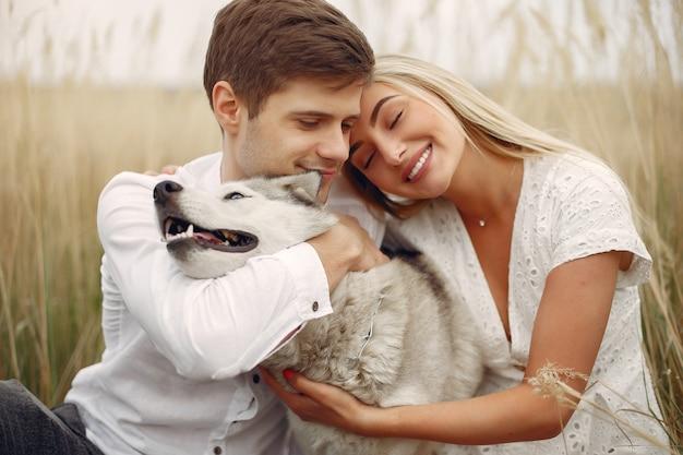 Paare auf einem herbstgebiet, das mit einem hund spielt