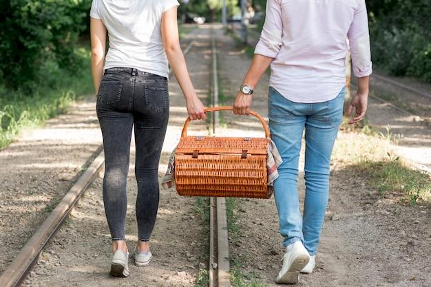 Paare auf einer eisenbahn, die einen picknickkorb trägt