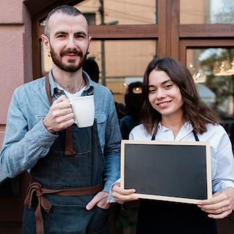 Paare außerhalb der kaffeestube, die schale und tafel hält