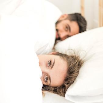 Paare bedeckt in der decke, die auf bett liegt