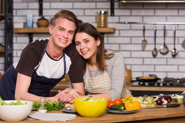 Paare bei tisch in der küche, die an der kamera lächelt