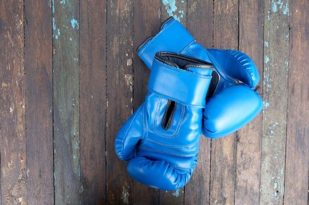 Paare boxhandschuhe auf einem rustikalen holztischhintergrund.