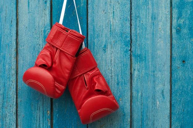 Paare boxhandschuhe, die in einer rustikalen hölzernen wand hängen