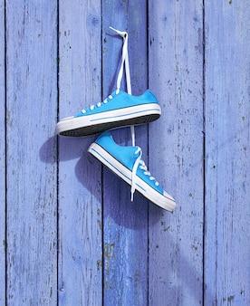 Paare der blauen textilturnschuhe, die an einem nagel hängen