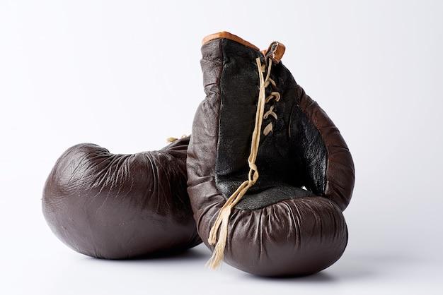 Paare der braunen ledernen boxhandschuhe der weinlese auf einer weißen oberfläche