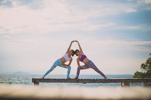 Paare der frau yoga spielend werfen auf strandpier mit moring sonnenlicht auf