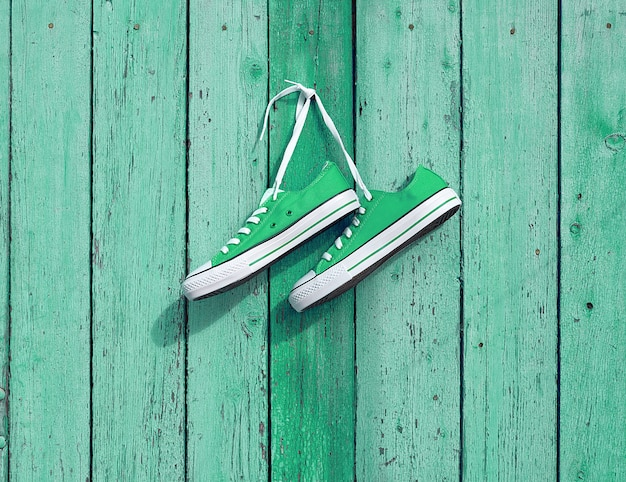 Paare der grünen textilturnschuhe, die an einem nagel auf der wand hängen