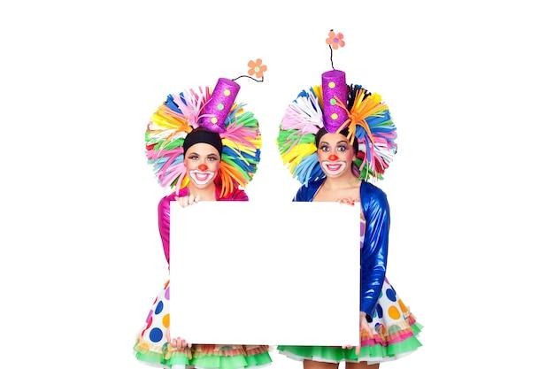 Paare der lustigen clowne mit einem unbelegten plakat getrennt auf weißem hintergrund