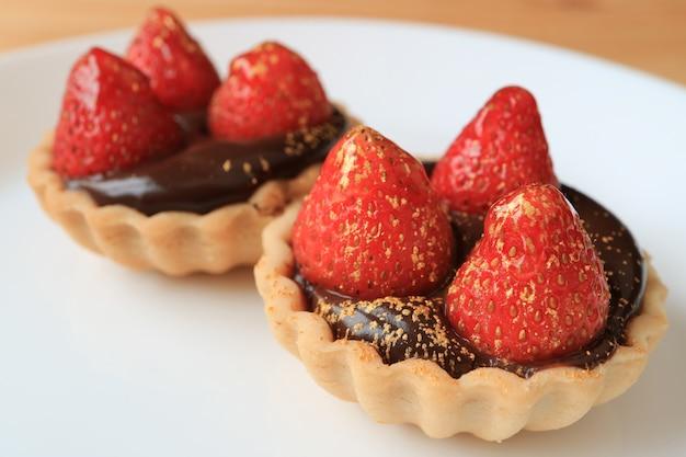 Paare der schokoladentörtchen, die mit frischen erdbeeren und essbarem goldpulver überstiegen wurden, dienten auf weißer platte