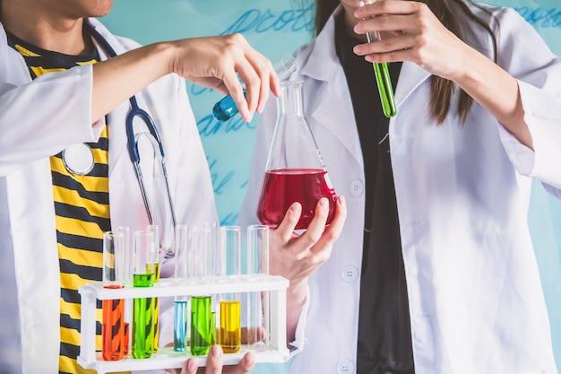 Paare der studenten, die am chemieunterricht arbeiten. bildungskonzept