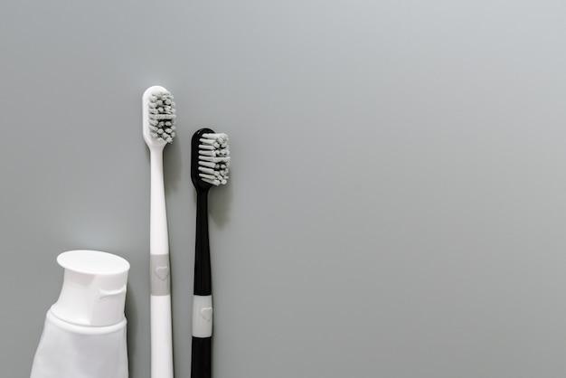 Paare der zahnbürste mit zahnpasta auf grauem hintergrund, gesundheitswesenkonzept