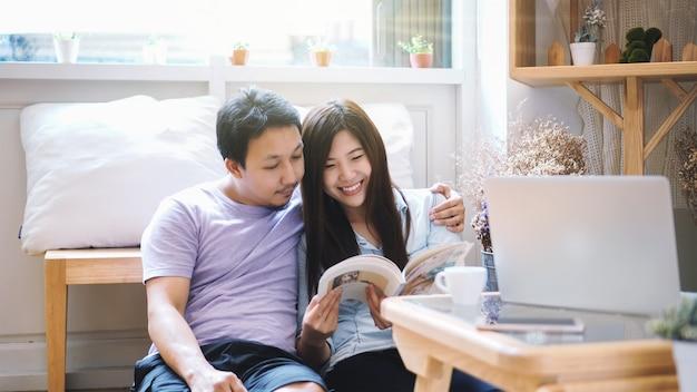 Paare des asiatischen liebhabers zusammen sitzend und morgens mit warmem gefühl lesend