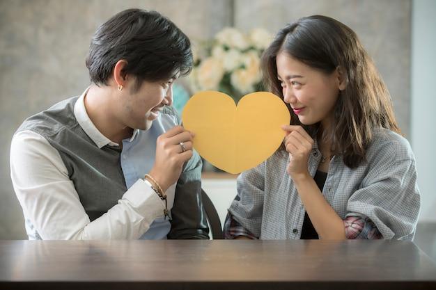 Paare des asiatischen mannes und der frau, die herzformpapier halten, schneiden mit glücksgefühl, leute lieben konzeptionelle