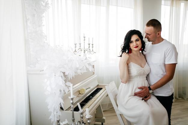 Paare des hübschen ehemanns und der hübschen pragnant frau, die am studio aufwerfen