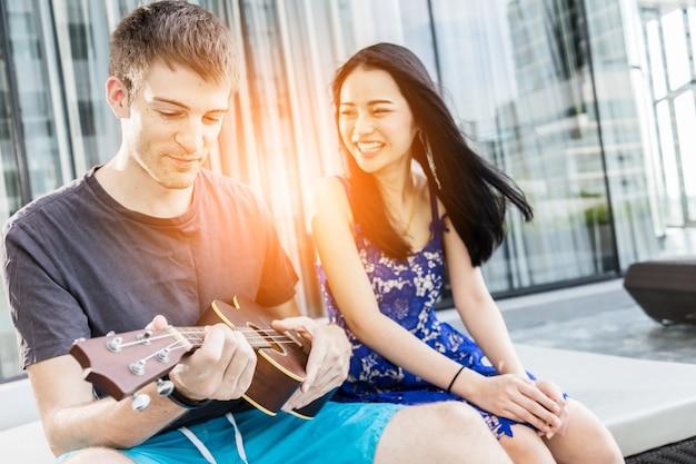 Paare des kaukasischen und asiatischen liebhabers spielen spaß mit glück und froher und ukulelesong im freienstandort