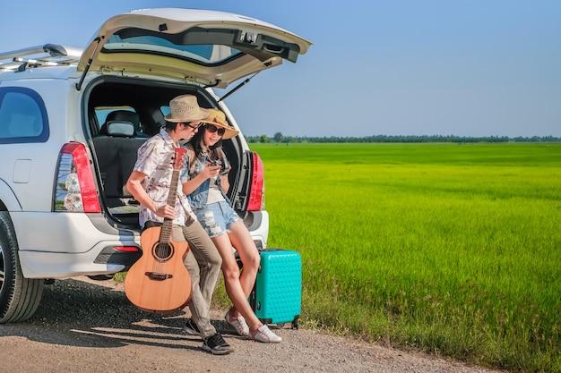 Paare des reisenden, der auf fließheck des autos sitzt und das bild auf kamera betrachtet