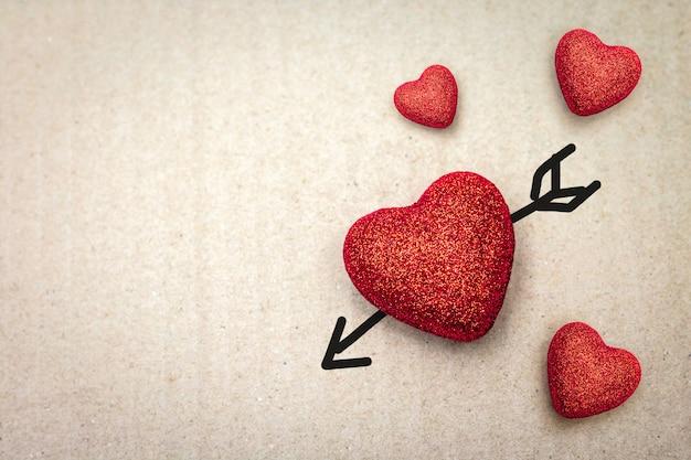 Paare des roten herzens mit amorpfeil auf papphintergrund.