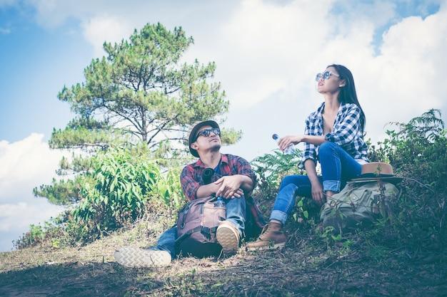Paare des touristen mit den rucksäcken, die auf einen berg sich entspannen und die ansicht genießen