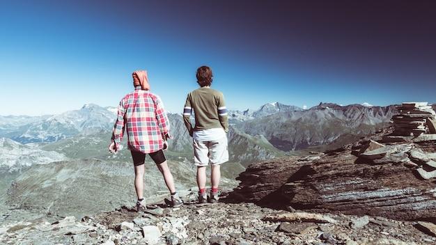 Paare des wanderers auf die gebirgsoberseite, die expasnive ansicht und bergspitzen betrachtet.