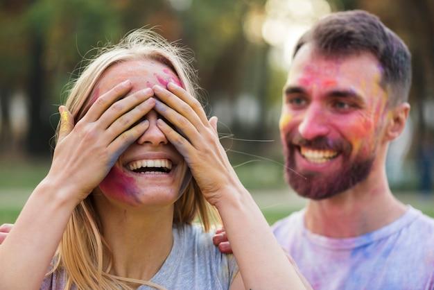 Paare, die am holi mit gemalten gesichtern aufwerfen