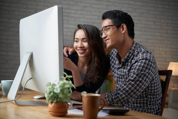 Paare, die am inländischen computer beim grasen des social media streicheln