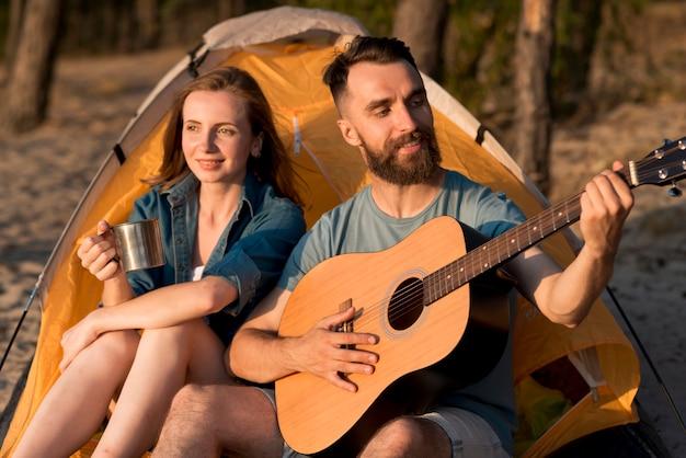 Paare, die am kampieren singen und trinken