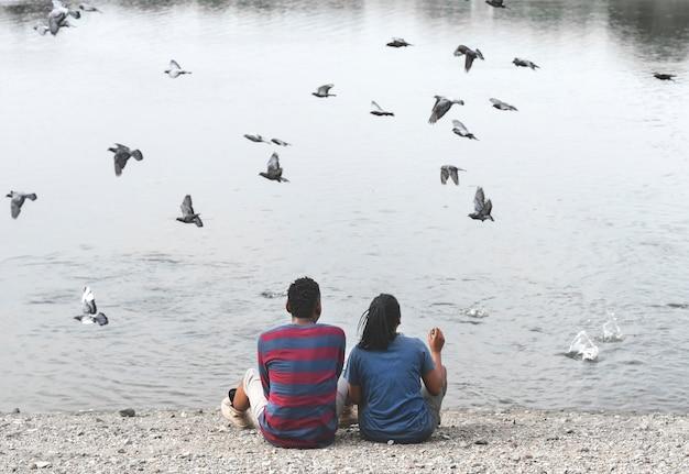 Paare, die am see mit den fliegenden vögeln sitzen