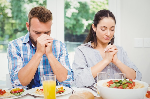 Paare, die am speisetische beten