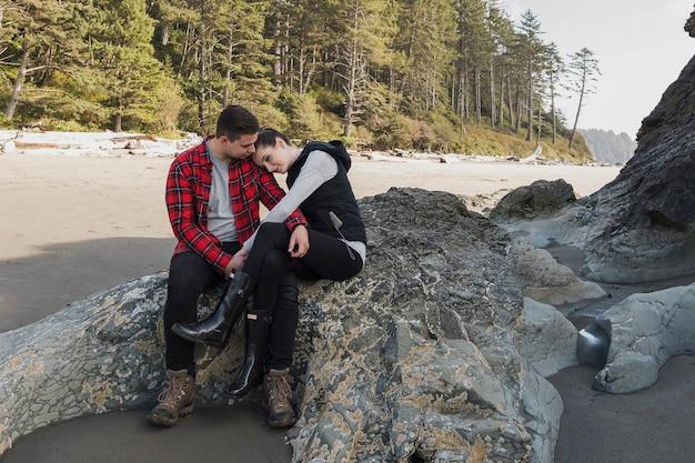 Paare, die am strand auf felsen sich halten