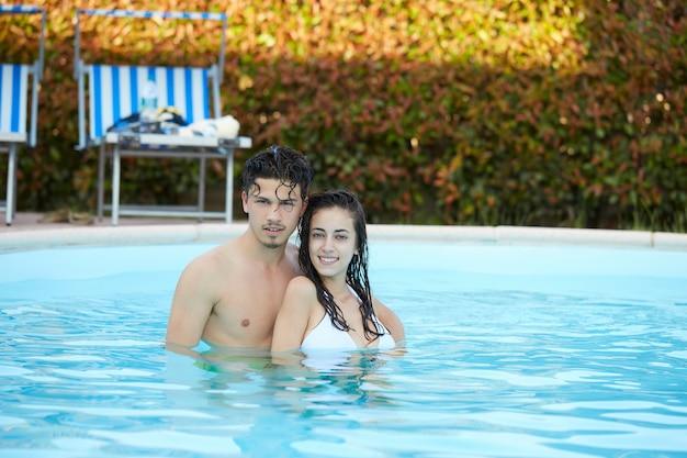Paare, die am swimmingpool sich entspannen