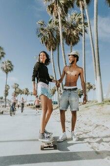 Paare, die am venedig-strand longboarding sind