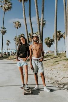 Paare, die am venice beach longboarding sind