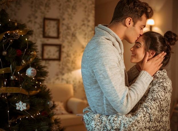 Paare, die am weihnachtsbaum streicheln