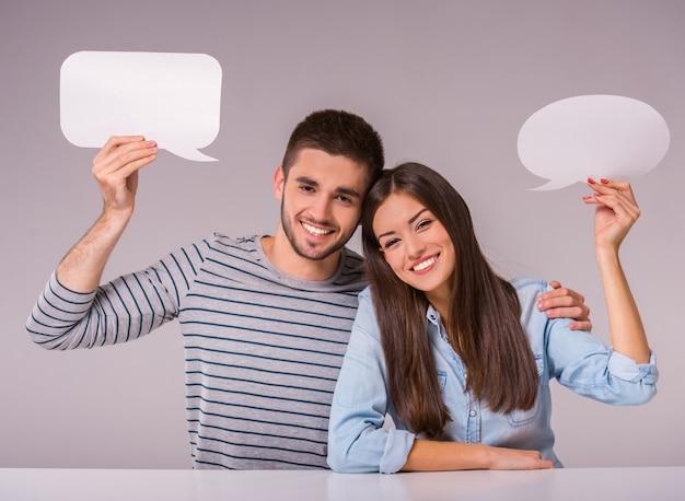 Paare, die an einem tisch hält leere spracheblasen sitzen