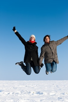 Paare, die an einem wintertag springen